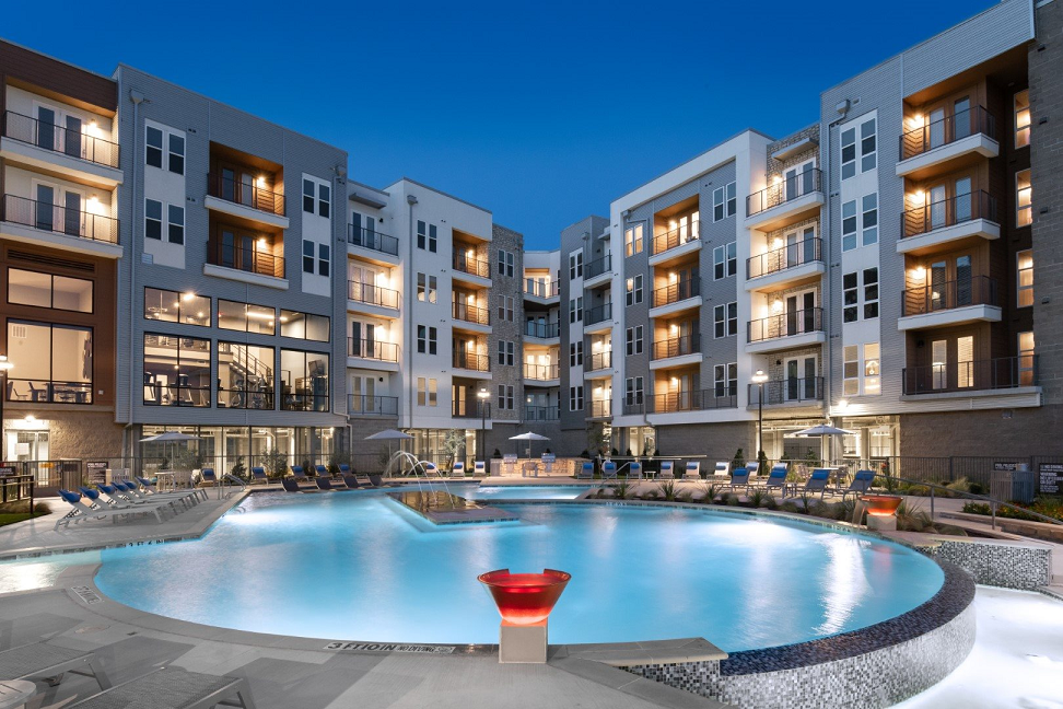 the view of fort worth multifamily infinity pool courtyard at night with led lighting